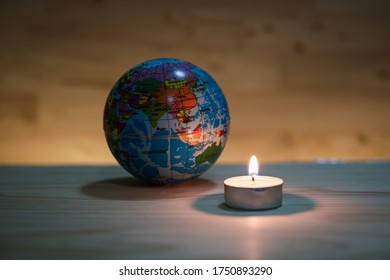 Globe model and candle light with wooden background