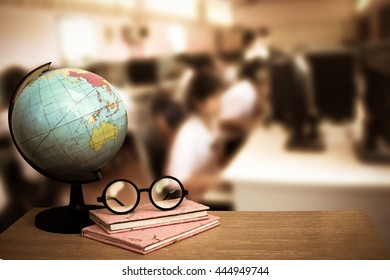 globe model and glasses on books with blur image of student in computer classroom background