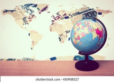 Globe on desk with world map on pile of banknote background