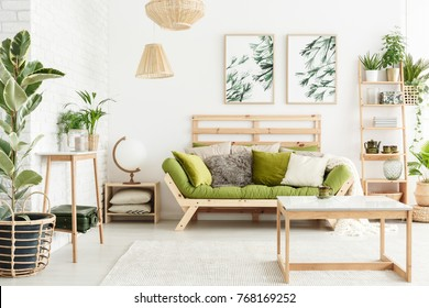 Globe shaped lamp placed on wooden table standing next to green couch in stylish living room interior