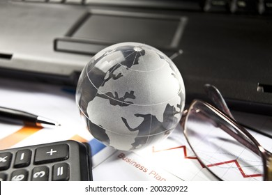 Globe and some business accessories on business documents with deep shadows.