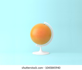 Globe sphere orb orange concepts on pastel blue background. minimal idea food and fruit concept. An idea creative to produce work within an advertising marketing communications or artwork design.