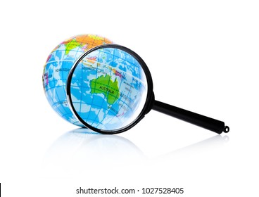 Globe under magnifying glass zooming Australia and New Zealand on white background