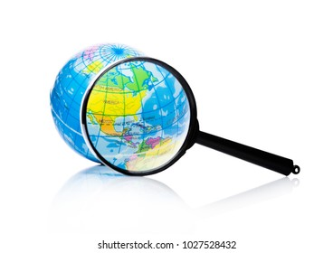 Globe under magnifying glass zooming North America, Mexico and Canada on white background