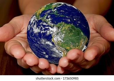 Globe in women's hands.Elements of this image furnished by NASA