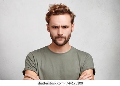 Gloomy bearded guy frowns face, being dissatisfied with results of competition, keeps hands crossed, demands explanation why he looses. Angry sullen man with stylish hairdo isolated over white wall