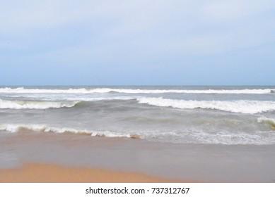 Gloomy blue sky and big white wave goes to orange sand beach in rainy season
