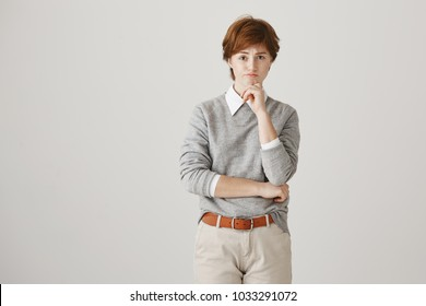 Gloomy and bothered redhead caucasian girl with freckles and boyish outfit holding hand on chin while looking upset at camera, recalling some bad memories, standing over gray background.