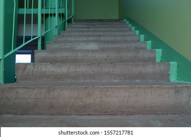 Gloomy concrete staircase in the entrance of an old multistory building. Dirty gray stairs and green walls. Low angle bottom view. Selective focus