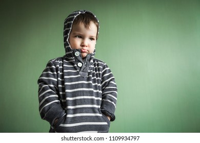 Gloomy cute little boy holding hands in pullover pockets.Free space for advertisement