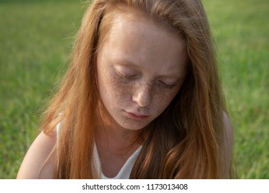 Gloomy face of sad ginger little girl with freckles with lowered eyes