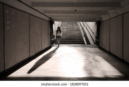 Gloomy long pedestrian underpass tunnel in dark colors. Young woman, illuminated by backlight, went down and walks alone, not expecting danger