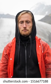 Gloomy man on a background of a glacier. Red raincoat, black warm clothes. Portrait of a tourist with a tense face. Blond with blue eyes, a beard. Mountain Altai. Cold snow.