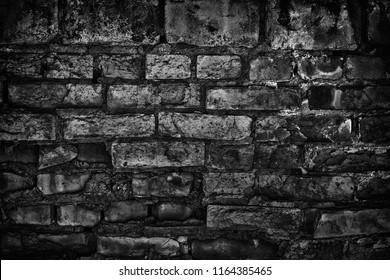 Gloomy old black brick wall. Crumbled aged rough brickwork texture. Sinister dark background