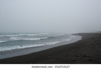 A gloomy picturesque landscape - rolling waves and footprints on a black volcanic sand on a misty morning. Khalaktyrsky beach in stormy weather, Pacific ocean, Kamchatka Peninsula, Far East Russia