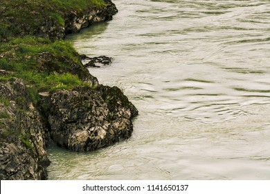 Gloomy view from above on rocky sinuous riverbank. Dark green of water. Eerie atmosphere in overcast rainy weather in cinematic faded tones. Landscape with shore of river in horror style.