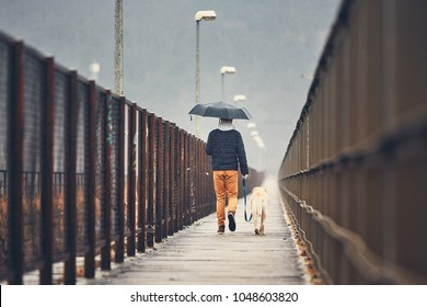 Gloomy weather in the city. Man with his dog (labrador retriever) walking in rain on the bridge. Prague, Czech Republic