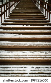Gloomy wooden staircase up. Winter season, forest. White snow on  steps of the stairs.