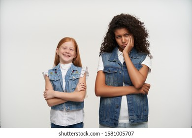 Gloomy young curly brunette female with dark skin looking sadly at camera and leaning her head on raised hand, posing over white background with cute cheerful redhead little girl