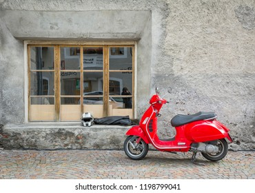 GLORENZA in South Tyrol, Italy - june 14, 2015: Piaggio vespa red scooter parked along the road.