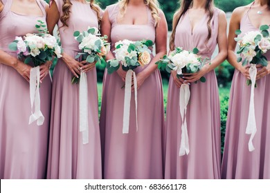 Glorious bridesmaids in pink dresses holding beautiful bunch of flowers