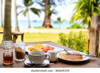 Glorious early morning breakfast at the beach resort in Thailand : freshly brewed black coffee, pancake, maple syrup, fresh fruits. Tropical vegetation and the sea visible on the background.