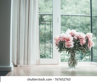 Glorious pastel pink bouquet of peonies in glass jug on  floor by window.  Flowers in interior design. Cozy home.