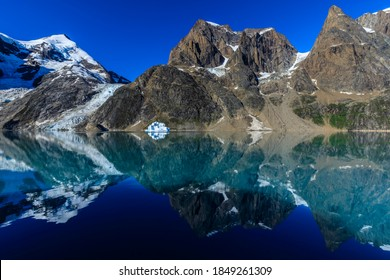 Glorious reflected mounatin scenery with glaciers and icebergs, of inspiring Skjoldungen Fjord in beautiful weather, remote East Greenland