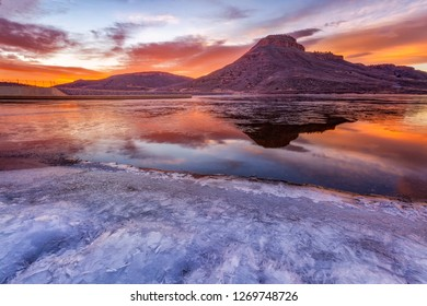 Glorious sunrise light on the Flatiron Butte located in Loveland, Colorado. The thin layer of ice on the reservoir glows in the ambient light