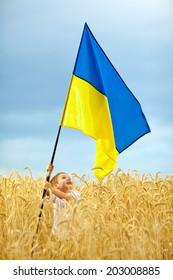 Glory to Ukraine! Boy waving Ukrainian flag on wheat field