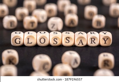 Glossary - word from wooden blocks with letters, alphabetical list with words meanings dictionary glossary concept, random letters around, top view on grey background