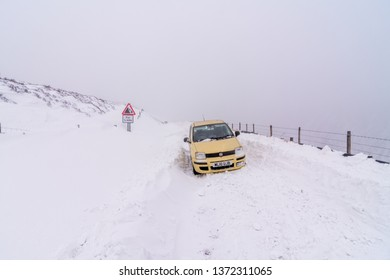 Glossop, Greater Manchester / United Kingdom - March 3 2018: Car stuck in a snowdrift on the notorious Sake Pass road in Peak District National Park