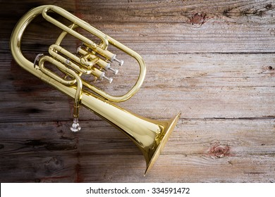 Glossy Baritone Horn Musical Instrument on a Wooden Floor with Copy Space on the Right Side.