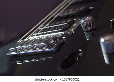 Glossy black electric guitar body closeup, with humbucker pickup and synchronised tremolo. Shallow focus.