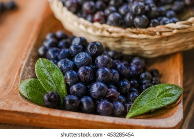 Glossy blueberries and leaves macro close up. Berries laying in wooden plate and basket. Healthy vegan vegetarian dish.