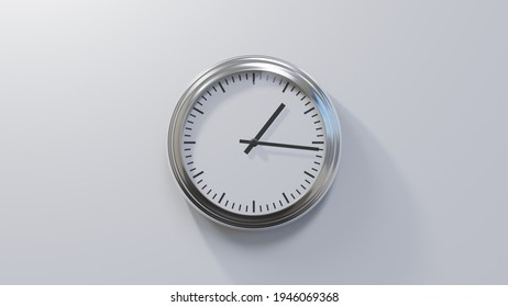 Glossy chrome clock on a white wall at sixteen past one. Time is 01:16 or 13:16