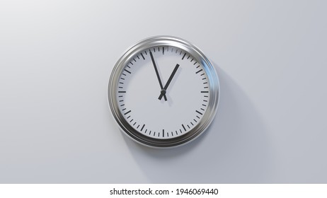 Glossy chrome clock on a white wall at fifty-seven past twelve. Time is 00:57 or 12:57