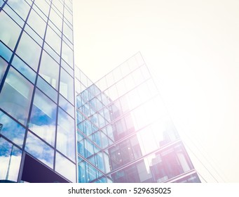 Glossy facade of an office building with sun coming through the glass.