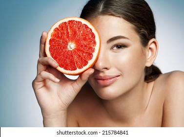 Glossy girl with grapefruit cut in half fruit in hand / photoset of attractive girl holding a cut piece of Sicilian orange on blue background