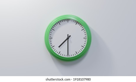 Glossy green clock on a white wall at half past seven. Time is 07:30 or 19:30