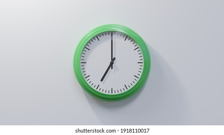 Glossy green clock on a white wall at seven o'clock. Time is 07:00 or 19:00