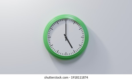 Glossy green clock on a white wall at five o'clock. Time is 05:00 or 17:00