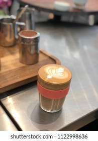Glossy latte art in a keep cup