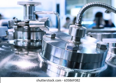 Glossy metal flanges on the body of the pharmaceutical reactor, close-up photo, selective focus. Abstract industrial background.