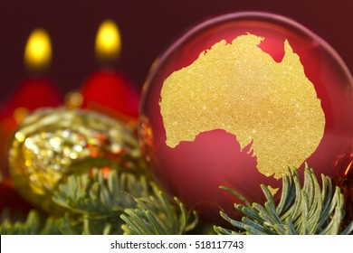 A glossy red bauble with the golden shape of Australia.(series)