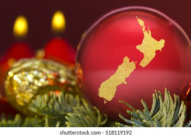 A glossy red bauble with the golden shape of New Zealand.(series)