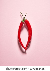 Glossy red hot chili peppers are lined in the shape of a female vagina