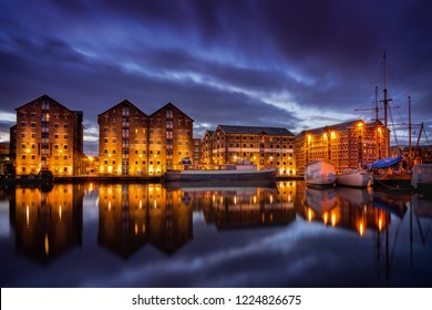 Gloucester docks at night with reflection of warehouses and boats
