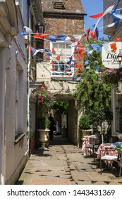 Gloucester Gloucestershire UK 1st JULY 2019  Bunting in the alleyway in Gloucester City Centre with The Beatrix Potter Museum & Shop and the Lily Tearoom