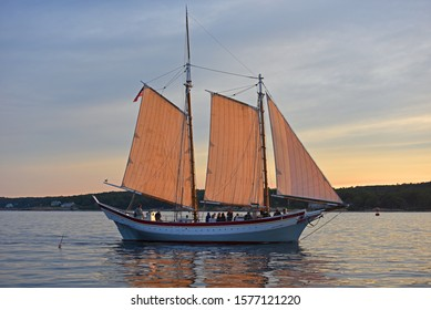 GLOUCESTER, MA, USA - AUG. 8, 2015: Schooner Ardelle sails at sunset in Gloucester Harbor, Massachusetts, USA.